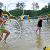 (Brad Davis/The Register-Herald) Youngsters Lily Gorrell, right, and Miranda McClaugherty, middle, watch as Pax resident Brooke Ebony passes the time practicing some hoop moves they and fellow festival-goers hang out by the lake during the final day of the Mountain Music Fest Saturday afternoon at Ace Adventure Resort.