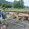 (Brad Davis/The Register-Herald) Fox Lanes Road resident Vicky Whitten, right, looks over what remains of a bridge that connected with Bass Lake Park Friday afternoon after it was washed out by flooding the day before. Campers at the park across the creek were not stranded however, as an access road on the other side of the park remained open.