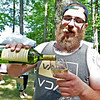(Brad Davis/The Register-Herald) A sun-soaked Drew Lawrence pours himself a glass during Daniel Vineyards' annual Spring Wine Festival Saturday afternoon in Crab Orchard.