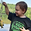 (Brad Davis/The Register-Herald) Five-year-old Tristan Clark shows off a blue gill he caught earlier in the day during the Kids Fishing Derby Saturday morning at Little Beaver State Park.