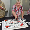 """(Brad Davis/The Register-Herald) Wyoming East cook Pat Shumate cuts a huge cake honoring Superintendent Frank """"Bucky"""" Blackwell during his retirement reception at Wyoming East High School Thursday evening."""