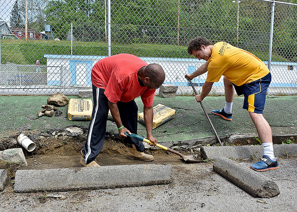 (Brad Davis/The Register-Herald) Volunteers Herbie Brooks, left, and Taylor Smith pry away at parking curbs as they work to clean up and improve some of the drainage system at the Mullens public pool during a Rural Appalachian Improvement League (R.A.I.L.) cleanup day around the town Saturday morning.