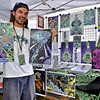 "(Brad Davis/The Register-Herald) Artist Pat Briney shows off some his work Friday evening at Mountian Music Festival. You can find his stuff at  <a href=""http://www.Loneskull.com"">http://www.Loneskull.com</a>."