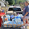 (Brad Davis/The Register-Herald) Volunteers Sherry Shelton, right, her husband Larry, lower left, and Randy Smith man a pickup truck full of supplies for those laboring through the cleanup process Sunday afternoon at the corner of Washington and Maple Streets in Alderson.