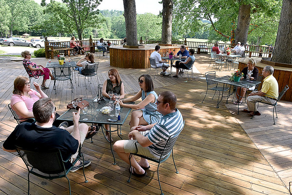(Brad Davis/The Register-Herald) Attendees relax in the shade on the big deck during Daniel Vineyards' annual Spring Wine Festival Saturday afternoon in Crab Orchard.