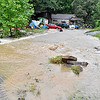 (Brad Davis/The Register-Herald) Flood water rushes from a hillside and down towards a residence along Bachman Road near Fayetteville during Thursday's severe rain and storms.