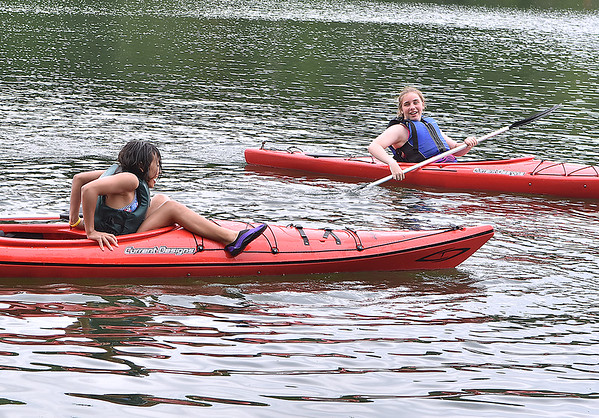 (Brad Davis/The Register-Herald) Chicago area girl scout Adriana Wanzell, right, gets a laugh out of Morgantown area girl scout Claire Dai as she practices climbing inside and out of her canoe during the final day of a Girl Scouts event at the Summit Bechtel Reserve Friday afternoon. The goal of the exercise is to climb from the seat of your canoe, crawl out to the front and touch your nose to the very end of your boat, a move designed to teach balance and boat handling skills on the water.