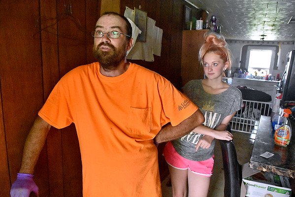 (Brad Davis/The Register-Herald) Commercial Avenue resident Michael Cox describes he and his family's efforts to clean up as his daughter Rachel looks on Saturday in Richwood.