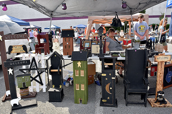 (Brad Davis/The Register-Herald) Wyoming County resident Angie Mullens looks on as she mans her table of handcrafted wood items during the 21st Annual Newspapers in Education Flea Market & Live Auction Saturday morning in the Marquee Cinemas parking lot.
