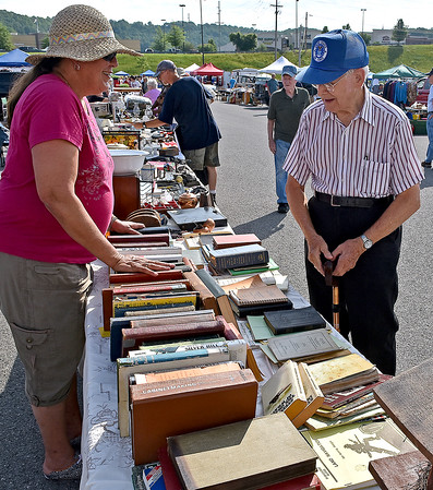 (Brad Davis/The Register-Herald) Vendor Kim Muncy and Prosperity resident Jim Jones chat as Jones browses items during the 21st Annual Newspapers in Education Flea Market & Live Auction Saturday morning in the Marquee Cinemas parking lot.