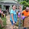 (Brad Davis/The Register-Herald) The Cox's and company on Commercial Avenue were in good spirits as they spent the day cleaning up Saturday in Richwood. From left are Jason Wright, Angelique Holcomb (background behind Wright), Beverly Cox (background in front of the door), Debra Cox, Rachel Cox and Michael Cox.
