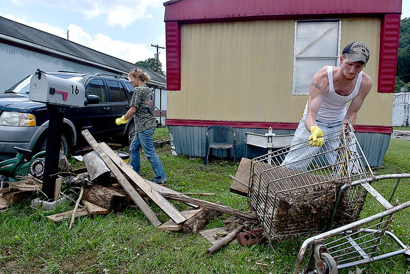 (Brad Davis/The Register-Herald) Residents Shawn Persinger and Kelly Taylor work to clean up the area along Commercial Avenue Saturday afternoon in Richwood.
