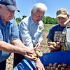 (Brad Davis/The Register-Herald) Guyan Conservation's Bill Stewart, left, state Department of Agriculture Commissioner Walt Helmick, middle, and active duty National Guardsman Tony Johnson inspect a batch of chieftain potato seeds before planting them during a Register-Herald visit to the historic farm June 8.