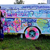 (Brad Davis/The Register-Herald) A very tall man, also known as The Mad Hatter, also known as Springfield, Missouri's Ryan Hobson, is photographed as he makes his way past the art bus Friday evening at Mountian Music Festival.