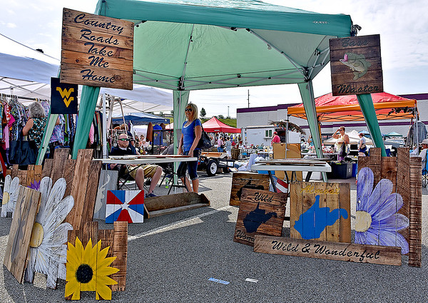 (Brad Davis/The Register-Herald) Handmade wooden signs and other items from creator Luke Shumate's (sitting at left behind the table) L.A. Rustic hang on display at his booth during the 21st Annual Newspapers in Education Flea Market & Live Auction Saturday morning in the Marquee Cinemas parking lot.