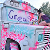 (Brad Davis/The Register-Herald) Huntington resident Brianna Taft adds to an old schoolbus on hand as a massive public art canvas parked in the main stage area of the Mountain Music Festival Friday evening at the Mountain Music Festival inside Ace Adventure Resort.