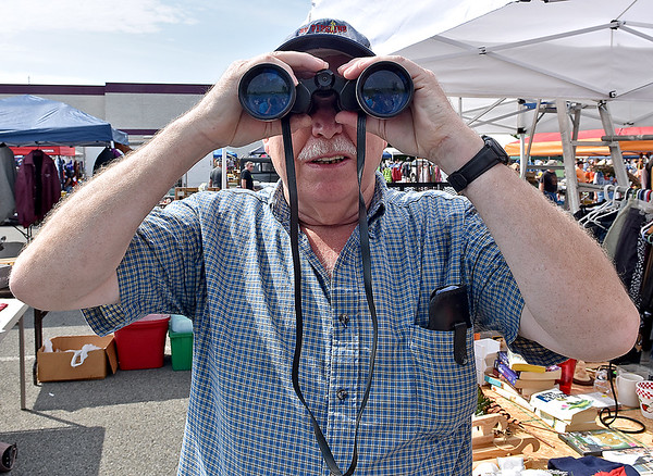 (Brad Davis/The Register-Herald) Pineville resident Lonzo Stacy finds the camera as he tries out a pair of binoculars available at the 21st Annual Newspapers in Education Flea Market & Live Auction Saturday morning in the Marquee Cinemas parking lot.
