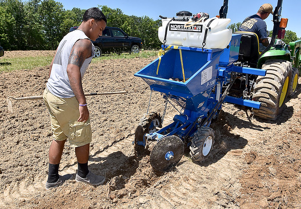 (Brad Davis/The Register-Herald) Active duty National Guardsman Tony Johnson drives the tractor while his son Devin follows closely behind making sure seeds from the planter are properly buried during a Register-Herald visit to the historic farm June 8.