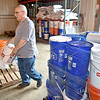 (Brad Davis/The Register-Herald) Scott Mayberry adds another bucket to the pallet as he and several other members of the United Methodist Church's Southern District of the West Virginia Conference help prepare hundreds of cleanup kits for distribution across areas most affected by flooding Friday afternoon at their disaster relief center on Airport Road.