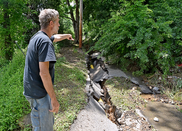 (Brad Davis/The Register-Herald) Richwood resident James Kinnel looks over what was once Walnut Street, a one lane road which is now mostly covered by a landslide, directly up the hill and behind his West Main Street apartment Saturday afternoon. The water line (inside the cracked asphault) broke when the landslide occured, sending more water spewing mud and debris in to his and others' homes before it was finally shut off some time later.