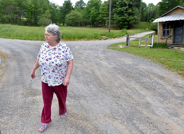 (Brad Davis/The Register-Herald) Abraham resident Pam Helmandollar walks the property around her Abraham Road home during a Register-Herald visit to the area June 2. The old Abraham post office is visible at far right. Her property is among several in the area that weren't reached by a new waterline project recently completed.