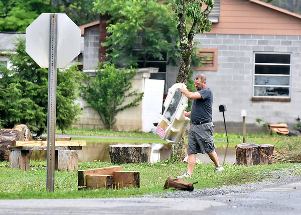 (Brad Davis/The Register-Herald) A resident retrieves a toy from remaining flood waters in Alderson Friday evening.