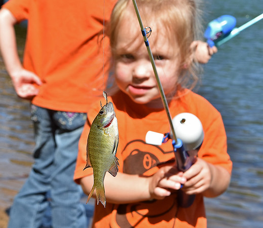 (Brad Davis/The Register-Herald) Three-year-old Ryleigh Farrish shows off a blue gill she caught during the Kids Fishing Derby Saturday morning at Little Beaver State Park.
