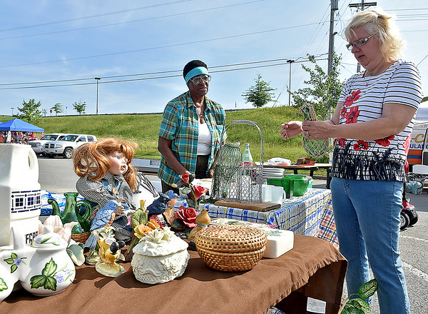 (Brad Davis/The Register-Herald) Rose Ann Harvey, right, browses items available at Queenester Jones (left) and her husband Sylvester's booth during the 21st Annual Newspapers in Education Flea Market & Live Auction Saturday morning in the Marquee Cinemas parking lot.