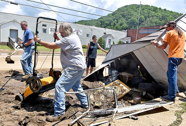 (Brad Davis/The Register-Herald) Fellow community members help Oakford Avenue resident Sam Wilson (2nd from left) retrieve items from his shed, which ended up in the street with everything still in it, Saturday afternoon in Richwood.