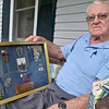(Brad Davis/The Register-Herald) 94-year-old World War II veteran Jesse Terry holds a display case containing some photos, medals and uniform items as he poses for a quick photo during a Register-Herald visit to his Midway home near Crab Orchard Thursday afternoon.