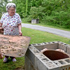 (Brad Davis/The Register-Herald) Abraham resident Pam Helmandollar removes the cover from the 100-year-old well situated beside her home during a Register-Herald visit to the area June 2.