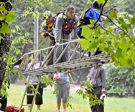 (Brad Davis/The Register-Herald) One at a time, rescue personnel from Fayetteville, Oak Hill and Ansted fire departments use a ladder truck to help stranded volunteers at the Fayette County Humane Society Animal Shelter across the flooded creek Thursday afternoon near Fayetteville. Several volunteers and employees were stranded when flood waters washed away the small bridge at the shelter. In this photo shelter volunteer Harley Waddell (middle on ladder) is escorted to safety.