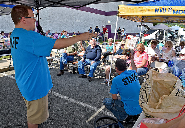 (Brad Davis/The Register-Herald) Auctioneer Chase Barton, left, keeps the prices flowing and the highly-anticipated live auction moving at a good pace during the 21st Annual Newspapers in Education Flea Market & Live Auction Saturday morning in the Marquee Cinemas parking lot.