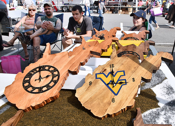 (Brad Davis/The Register-Herald) Hand crafted West Virginia clocks and other specialty items made by Matt (second from right) and Stephanie (far right) Stadelman sit on display during the 21st Annual Newspapers in Education Flea Market & Live Auction Saturday morning in the Marquee Cinemas parking lot.