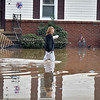 (Brad Davis/The Register-Herald) A resident slogs down a flooded street in Alderson Friday evening.