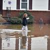 (Brad Davis/The Register-Herald) A resident slogs down a flooded street in Alderson Friday evening.