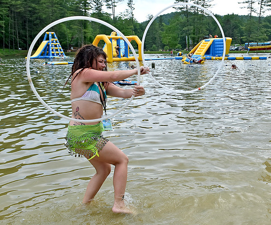 (Brad Davis/The Register-Herald) Pax resident Brooke Ebony passes the time practicing some hoop moves as she and fellow festival-goers hang out by the lake during the final day of the Mountain Music Fest Saturday afternoon at Ace Adventure Resort.