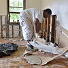 (Brad Davis/The Register-Herald) Daryl Terry, son-in-law of resident Roy Grimes, goes to work tearing out all the waterlogged sections of drywall inside Grimes' Washington Street home Sunday afternoon in Alderson.