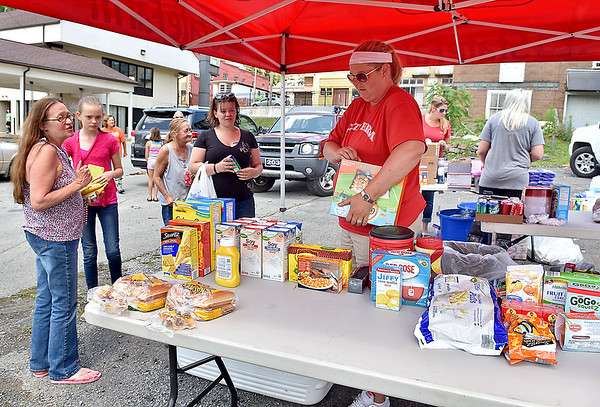 (Brad Davis/The Register-Herald) Volunteer and Pennsylvania resident Stacie Hickman (middle in red), along with several others, set up a table with water, food and other supplies Saturday morning in Richwood. Thanks to their trailor full of supplies, residents were able to stop by to pick up anything they might need to help through a long, difficult day of cleaning up, and her group also grilled hot dogs for anyone who was hungry.