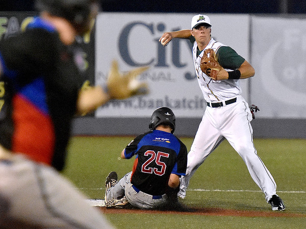 (Brad Davis/The Register-Herald) West Virginia shortstop Paul Trick retires Champion City's Cale Dineen (#25) for the first out of a double play Saturday night at Linda K. Epling Stadium.