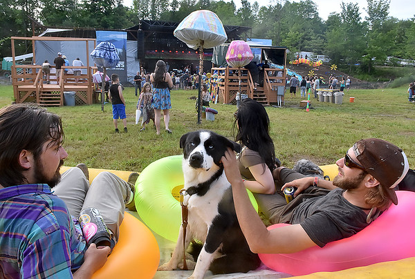 (Brad Davis/The Register-Herald) Bluefield resident Scott Ferris, left, Charleston residents Tyler Bullock, right, and Jamie Bowles (back turned middle), lounge with companions Classie, middle, and Finn, hidden at right, during Mountain Music Festival Friday evening inside Ace Adventure Resort.