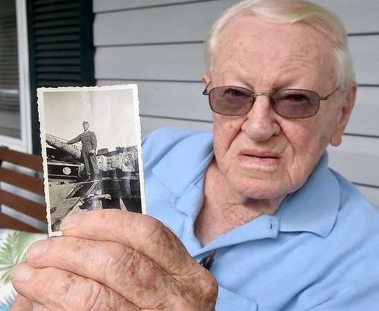 (Brad Davis/The Register-Herald) 94-year-old World War II veteran Jesse Terry holds up a photo of himself atop a captured German tank during a Register-Herald visit to his Midway home near Crab Orchard Thursday afternoon.