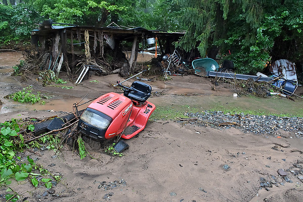 (Brad Davis/The Register-Herald) Property is left strewn about and buried in mud Friday afternoon in the aftermath of Thursday's flooding in Owens Branch near Hinton.