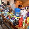 (Brad Davis/The Register-Herald) Elaine Stonestreet, right, packs a bucket with cleaning supplies as she and several other members of the United Methodist Church's Southern District of the West Virginia Conference help prepare hundreds of cleanup kits for distribution across areas mst affected by flooding Friday afternoon at their disaster relief center on Airport Road.