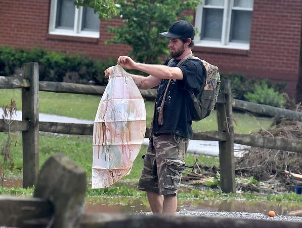 (Brad Davis/The Register-Herald) A resident looks over a random piece of debris in Alderson Friday evening.