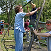 (Brad Davis/The Register-Herald) From right, volunteers John Paul Lusk, 11, John Morgan (ladder), Norma Sneed-Moore (background behind ladder) and Trudy Blackwell, along with several others prep the playground equipment at Mullens Middle School for fresh paint during a Rural Appalachian Improvement League (R.A.I.L.) cleanup day around the town Saturday morning. Several teams of volunteers from around the area spent the day putting in a little elbow grease to improve and spruce up public and residential areas around Mullens.