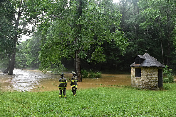 (Brad Davis/The Register-Herald) A pair of Fayetteville firefighters size up the situation around the creek next to the Fayette County Humane Society Animal Shelter Thursday afternoon, where flood waters washed away the bridge and temporarily stranded a handful of volunteers and employees beofre being rescued.