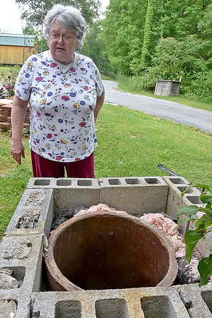 (Brad Davis/The Register-Herald) Abraham resident Pam Helmandollar shows her 100-year-old well situated beside her home during a Register-Herald visit to the area June 2.