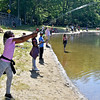 (Brad Davis/The Register-Herald) Ten-year-old Beckley resident Camryn Burks, left, casts her line into the water as twin sister Amiya, right of Camryn, and nine-year-old brother B.J. fish along side her on the crowded banks of the lake during the Kids Fishing Derby Saturday morning at Little Beaver State Park.