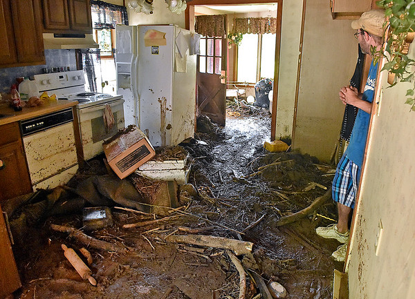 (Brad Davis/The Register-Herald) Brooks resident James Graham, leaning at right, looks over his muddy home as he describes the night flooding forced he and his family to escape through a window Sunday afternoon near Hinton.